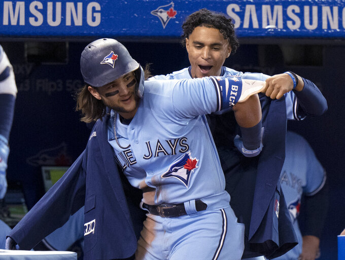 """FILE - In this Sept. 29, 2021, file photo, Toronto Blue Jays' Santiago Espinal puts the home run jacket onto Bo Bichette (11) after he homered during the third inning of the team's baseball game against the New York Yankees in Toronto. Even in baseball, where traditionalists sneer at anything that might seem disrespectful or undignified, teams haven't been afraid to show some personality. The Phillies have a straw Home Run Hat, the Rockies have """"homer shades"""" sunglasses  and the Blue Jays have a blue blazer for members of their """"HR Club."""" The New York Mets ride a stuffed pony through the dugout to celebrate homers; the San Diego Padres pass around a seven-pound bejeweled necklace dubbed the """"Swagg Chain."""" (Frank Gunn/The Canadian Press via AP, File)"""