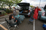 """Opera fans Linda McDonald-Hummingbird, left, and Jane Tustin pack up a meal in the parking lot of the Santa Fe Opera is seen on Friday, June 18, 2021, outside Santa Fe, N.M. The Santa Fe Opera is running its first show since the pandemic began, in a venue uniquely suited for virus safety: the performance space is outdoors, albeit covered by a roof. The pre-show """"tailgate"""" drew hundreds of people and many glasses of champagne (The Marriage of Figaro), must go on. (AP Photo/Cedar Attanasio)"""