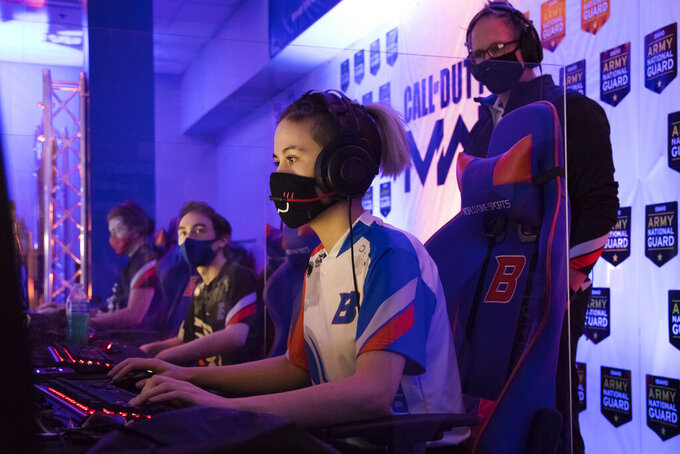 "Boise State esports coach Doc Haskell, right, watches scholarship graduate student Artie ""N3rdybird"" Rainn compete in a match in Boise, Idaho, on Thursday, March 4, 2021. Colleges and universities rushing to invest in the booming arena of varsity esports are overwhelmingly committing opportunities and scholarships to male players, according to data collected by The Associated Press. Boise State was among the more equal schools in the AP's survey, with 16 male players, five female players and three who identified as nonbinary.(AP Photo/Otto Kitsinger)"