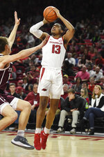 Arkansas guard Mason Jones (13) shoots over Texas A&M defender Chris Collins during the first half an NCAA college basketball game, Saturday, Feb. 23, 2019, in Fayetteville, Ark. (AP Photo/Michael Woods)