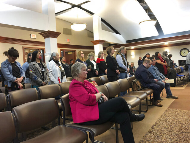 Opponents to a bill that revamps the state's riot laws stand in respect to several people who spoke against the proposal, Tuesday, March 3, 2020, in the Capitol in Pierre, S.D. (AP Photo/Stephen Groves)