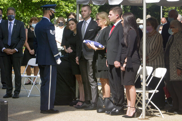Heather Merrill, widow of former Gov. Steve Merrill, receives an American flag at his memorial service outside the Statehouse on Friday, Sept. 11, 2020, in Concord, N.H. Merrill, a Republican who served two terms in the 1990s, died Sept. 5 at age 74. (AP Photo/Holly Ramer)