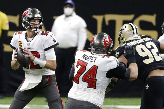 Tampa Bay Buccaneers quarterback Tom Brady (12) works in the pocket as New Orleans Saints defensive end Marcus Davenport (92) applies pressure during the first half of an NFL divisional round playoff football game, Sunday, Jan. 17, 2021, in New Orleans. (AP Photo/Butch Dill)
