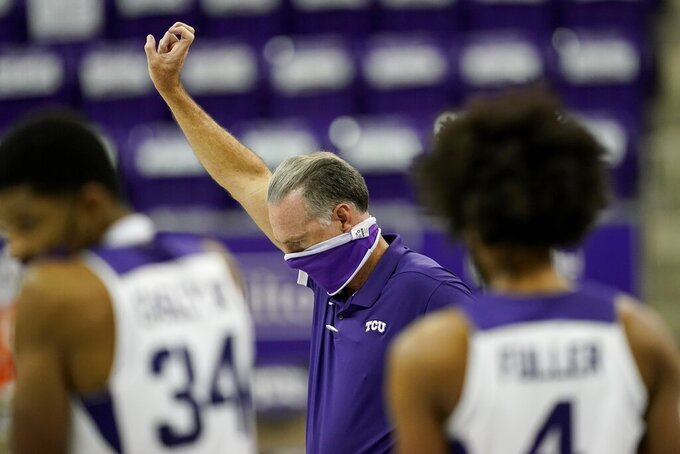 "TCU coach Jamie Dixon and players Kevin Easley (34) and PJ Fuller (4) join the rest of the team gesturing the ""Horned Frog"" symbol as the school song plays after the team's NCAA college basketball game against Northwestern State in Fort Worth, Texas, Thursday, Dec. 3, 2020. (AP Photo/Tony Gutierrez)"