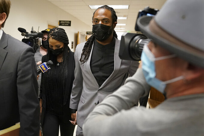 Richard Sherman, center right, walks with his wife Ashley, following a King County District Court hearing Friday, July 16, 2021, in Seattle. The NFL football cornerback, who has played with the Seattle Seahawks and the San Francisco 49ers, was arraigned on five criminal charges Friday after he was arrested Wednesday after police said he crashed his car in a construction zone along a busy highway east of Seattle and then tried to break into his in-laws' home in the suburb of Redmond, Wash. (AP Photo/Ted S. Warren)