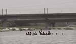 People play in the River Yamuna on a hot summer day in New Delhi, India, Thursday, May 28, 2020. India grappled with scorching temperatures and the worst locust invasion in decades as authorities prepared for the end of a months long lockdown despite recording thousands of new infections every day. (AP Photo/Manish Swarup)