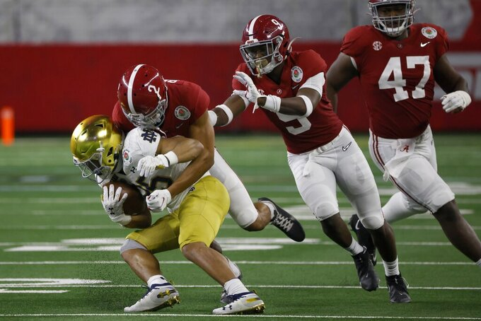 Notre Dame running back Chris Tyree (25) is stopped by Alabama defensive back Patrick Surtain II (2) with help from defensive back Jordan Battle (9) and defensive lineman Byron Young (47) in the second half of the Rose Bowl NCAA college football game in Arlington, Texas, Friday, Jan. 1, 2021. (AP Photo/Ron Jenkins)