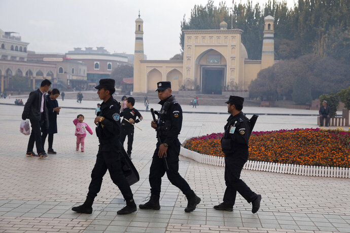 FILE - In this Nov. 4, 2017 file photo, Uighur security personnel patrol near the Id Kah Mosque in Kashgar in western China's Xinjiang region. China's northwestern region of Xinjiang has revised legislation to allow the detention of suspected extremists in