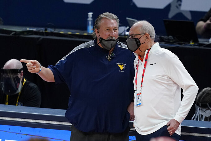 West Virginia head coach Bob Huggins, left, talks with Syracuse head coach Jim Boeheim, right, before a second-round game in the NCAA men's college basketball tournament at Bankers Life Fieldhouse, Sunday, March 21, 2021, in Indianapolis. (AP Photo/Darron Cummings)