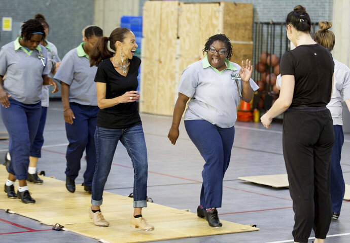Jamie Monghan, center, an inmate at Ohio Reformatory for Women, laughs as she learns a new step during the first of 12 tap dance classes, taught by instructor, Jessica Kehn, right, part of the Tapestry Program, Friday, September 20, 2019. (Courtney Hergesheimer/The Columbus Dispatch via AP)