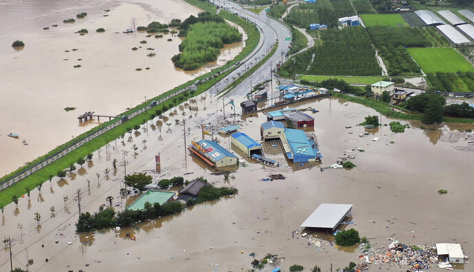 A village area is flooded near Seomjin River, left, due to heavy rain in Hadong, South Korea, Saturday, Aug. 8, 2020. (Kim Dong-min/Yonhap via AP)