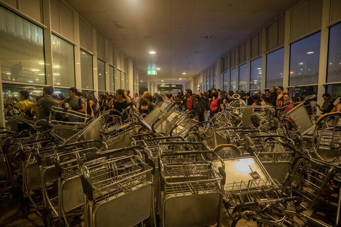 Trolleys block an entrance at El Prat airport, outskirts of Barcelona, Spain, Monday, Oct. 14, 2019. Spain's Supreme Court on Monday sentenced 12 prominent former Catalan politicians and activists to lengthly prison terms for their roles in a 2017 bid to gain Catalonia's independence, sparking protests across the wealthy Spanish region. (AP Photo/Bernat Armangue)
