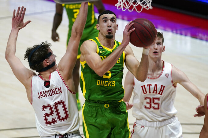 Oregon guard Chris Duarte, center, goes to the basket as Utah's Mikael Jantunen (20) and Branden Carlson (35) defend in the first half during an NCAA college basketball game Saturday, Jan. 9, 2021, in Salt Lake City. (AP Photo/Rick Bowmer)