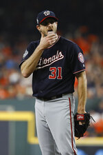 Washington Nationals starting pitcher Max Scherzer wipes his face during the first inning of Game 1 of the baseball World Series against the Houston Astros Tuesday, Oct. 22, 2019, in Houston. (AP Photo/Matt Slocum)
