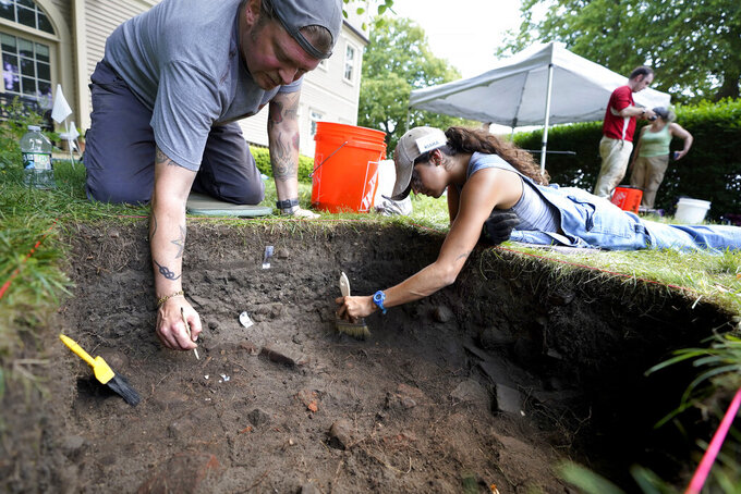 University of Massachusetts Boston graduate students Nicholas Densley, of Missoula, Mont., left, and Kiara Montes, of Boston, right, use brushes while searching for artifacts at an excavation site, Wednesday, June 9, 2021, on Cole's Hill, in Plymouth, Mass. The archaeologists are part of a team excavating the grassy hilltop that overlooks iconic Plymouth Rock one last time before a historical park is built on the site. (AP Photo/Steven Senne)