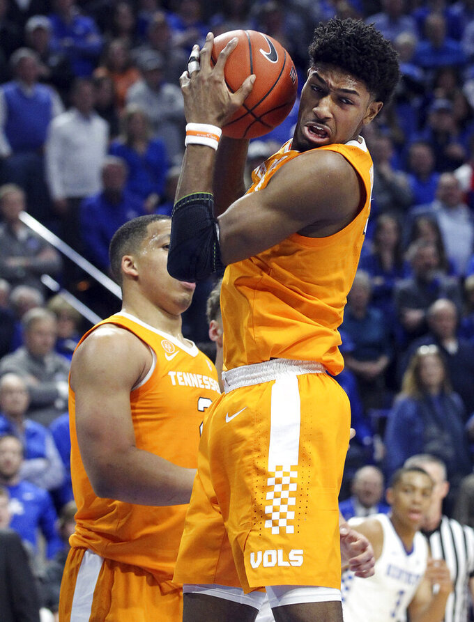Tennessee's Kyle Alexander, right, pulls down a rebound near teammate Grant Williams during the first half of an NCAA college basketball game against Kentucky in Lexington, Ky., Saturday, Feb. 16, 2019. (AP Photo/James Crisp)