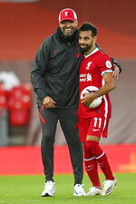 Liverpool's manager Jurgen Klopp, left, and Liverpool's Mohamed Salah celebrate at the end of the English Premier League soccer match between Liverpool and Leeds United, at the Anfield stadium, in Liverpool, Saturday, Sept. 12, 2020. (Shaun Botterill, Pool via AP)