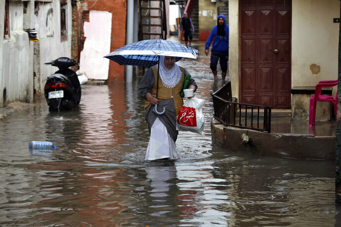 People walk through floodwaters in Beirut's southern suburb of Ouzai, Lebanon, Monday, Dec. 9, 2019. A rainstorm paralyzed parts of Lebanon's capital Beirut on Monday, turning streets to small rivers, stranding motorists inside their vehicles and damaging homes in some areas. (AP Photo/Bilal Hussein)