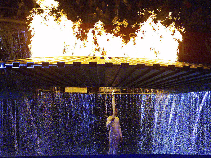 Australian runner Cathy Freeman stands under the Olympic torch after lighting the flame at the opening ceremonies for the 2000 Summer Olympics in Sydney, Australia, Sept. 15, 2000. (AP Photo/Kevin Frayer)