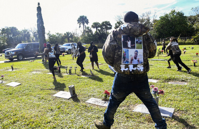 Spectators run from the scene after a shot was fired during the burial service of Sincere Pierce at Riverview Memorial Gardens in Cocoa, Fla., Saturday, Nov. 28, 2020. Pierce was one of two teens shot and killed by a Brevard County Sheriff's deputy on Nov. 13. (Craig Bailey/Florida Today via AP)