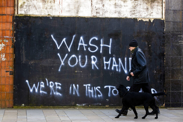 A man walking a dog past graffiti with the writing,
