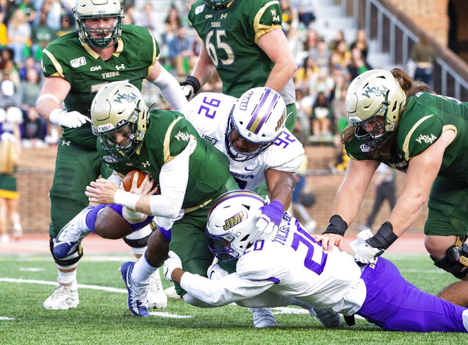 William & Mary quarterback Kilton Anderson, left, is brought down by James Madison's Diamonte Tucker-Dorsey (20) and Semaj Sorhaindo (92) during the first half of an NCAA college football game in Williamsburg, Va., on Saturday, Oct. 19, 2019. (Mike Caudill/The Virginian-Pilot via AP)