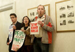 A trio of protesters yell outside of a meeting with Canada's Prime Minister Justin Trudeau and California Gov. Jerry Brown in San Francisco, Friday, Feb. 9, 2018. (AP Photo/Jeff Chiu, Pool)