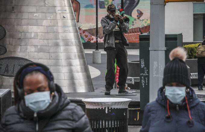 "FILE - In this April 18, 2020 file photo Harlem resident who goes by the name New World Warrior, center, plays ""Lift Every Voice And Sing"" on his trumpet at one of multiple stops along 125th Street, blaring the song repeatedly as people walk on by, in New York. The Black national anthem was born more than a century ago, but the popular hymn within the African American community called ""Lift Every Voice and Sing"" has been resurrected as a beacon of hope for all races during nationwide protests. (AP Photo/Bebeto Matthews, File)"
