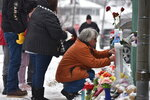 Mourners place a flower at the crosses outside of the Henry Pratt company in Aurora, Ill., on Sunday, Feb. 17, 2019, in memory of the five employees killed on Friday. (Jeff Knox/Daily Herald via AP)