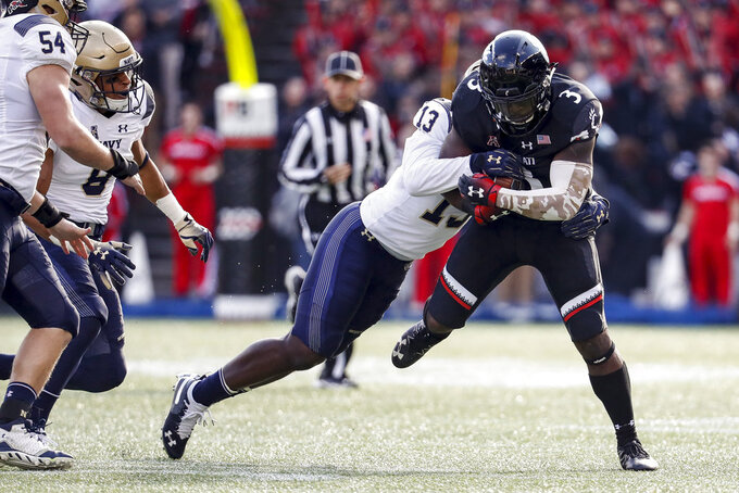 Cincinnati running back Michael Warren II (3) is tackled by Navy safety Juan Hailey (13) in the first half of an NCAA college football game, Saturday, Nov. 3, 2018, in Cincinnati. (AP Photo/John Minchillo)