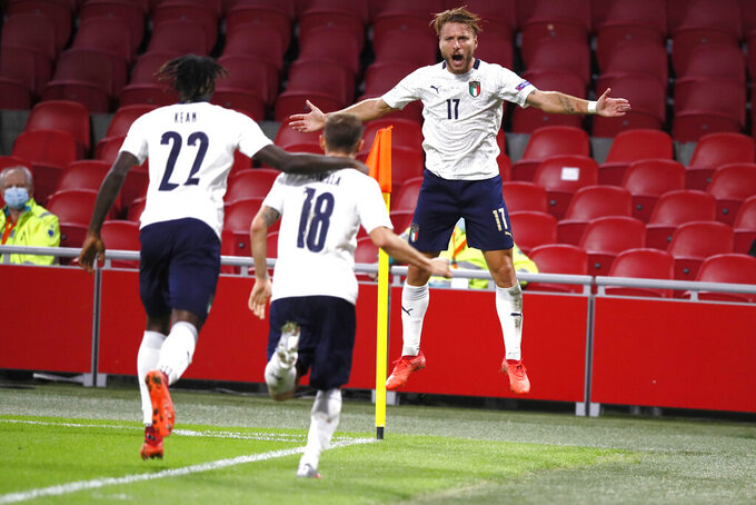 Italy's Nicolo Barella, center, is celebrated by teammates Italy's Ciro Immobile, right, and Italy's Moise Kean, after scoring his side's first goal during the UEFA Nations League soccer match between The Netherlands and Italy at the Johan Cruijff ArenA in Amsterdam, Netherlands, Monday, Sept. 7, 2020. (AP Photo/Peter Dejong)