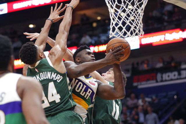 New Orleans Pelicans forward Zion Williamson goes to the basket between Milwaukee Bucks forward Giannis Antetokounmpo (34) and center Brook Lopez (11) in the first half of an NBA basketball game in New Orleans, Tuesday, Feb. 4, 2020. (AP Photo/Gerald Herbert)