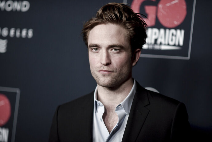 """FILE - In this Nov. 16, 2019 file photo, Robert Pattinson attends the 13th Annual Go Gala at NeueHouse Hollywood in Los Angeles.  The U.K. production of """"The Batman"""" starring Pattinson, is starting up again after being shut down earlier this month when an individual tested positive for COVID-19. A spokesperson for Warner Bros. said Thursday, Sept. 17, 2020,  that filming had resumed after a hiatus for quarantine precautions.  (Photo by Richard Shotwell/Invision/AP)"""