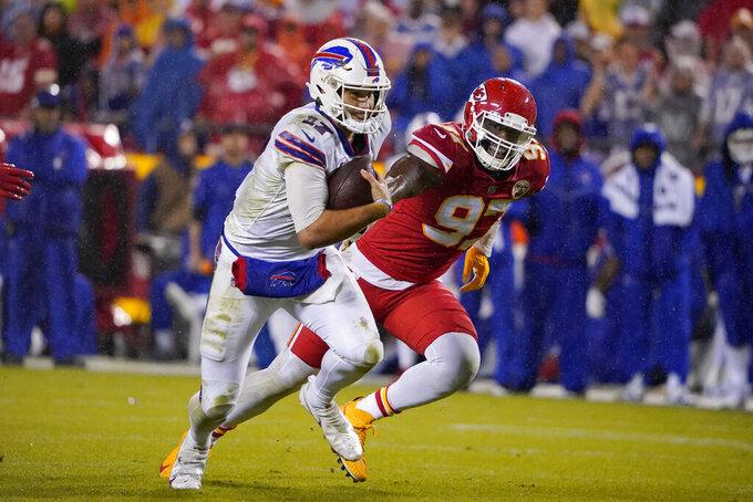 Buffalo Bills quarterback Josh Allen, left, runs with the ball as Kansas City Chiefs defensive end Alex Okafor (97) defends during the second half of an NFL football game Sunday, Oct. 10, 2021, in Kansas City, Mo. (AP Photo/Ed Zurga)