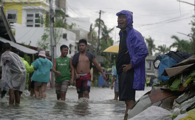 Residents wade along a flooded village caused by typhoon Vongfong as it passed by Sorsogon province, eastern Philippines on Friday May 15, 2020. More than 150,000 people were riding out a weakening typhoon in emergency shelters in the Philippines on Friday after a mass evacuation that was complicated and slowed by the coronavirus. (AP Photo/Melchor Hilotin)