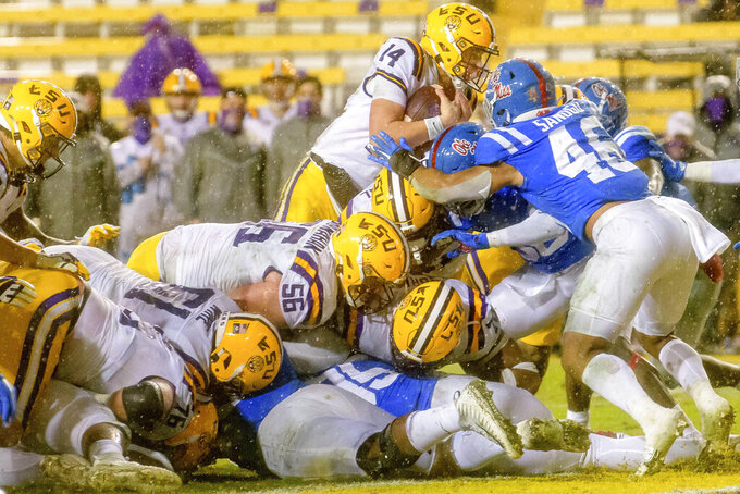 LSU quarterback Max Johnson (14) leaps and scores a touchdown against Mississippi during the second half of an NCAA college football game in the rain in Baton Rouge, La., Saturday, Dec. 19, 2020. (AP Photo/Matthew Hinton)