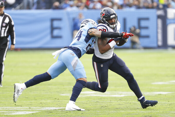 Tennessee Titans strong safety Kenny Vaccaro (24) closes in on Houston Texans tight end Jordan Akins, right, in the first half of an NFL football game Sunday, Dec. 15, 2019, in Nashville, Tenn. (AP Photo/James Kenney)