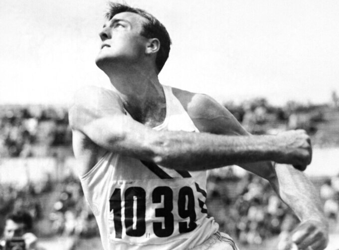 FILE - In this July 26, 1952, file photo, Bob Mathias, defending Olympic decathlon champion, heaves the discus during the decathlon competition at the Summer Olympic games in Helsinki, Finland. (AP Photo/File)