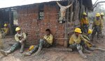 In this Aug. 30, 2019 photo, soldiers take a break from fighting fires in the Chiquitania Forest, on the outskirts of Robore, Bolivia. While some of the fires are burning in Bolivia's share of the Amazon, the largest blazes were in the Chiquitania region of southeastern Bolivia. It's zone of dry forest, farmland and open prairies that has seen an expansion of farming and ranching in recent years. (AP Photo/Juan Karita)