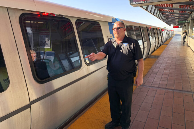 In this photo taken Monday, Nov. 4, 2019, transit supervisor John O'Connor talks with reporters about pulling a man from the tracks in front of a coming train at the Bay Area Rapid Transit Coliseum station in Oakland, Calif. O'Connor was hailed as a hero for pulling a drunken man from the tracks an instate before a train sped into the station. The Bay Area Rapid Transit released surveillance video showing supervisor O'Connor spring to action Sunday after a man fell onto the tracks.   (AP Photo/Terry Chea)