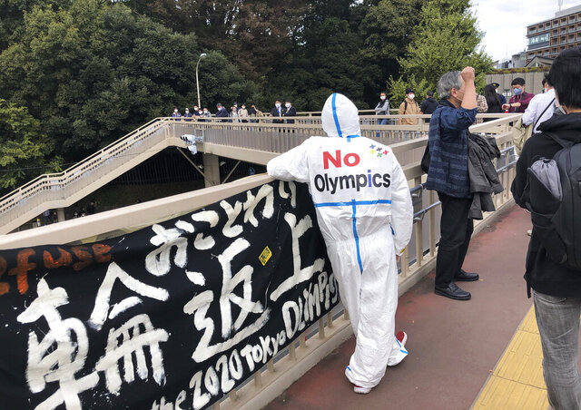 An anti-Olympic protester stands outside the Yoyogi National Stadium on in Tokyo on Sunday, Nov. 8, 2020. About 30 anti-Olympic protesters showed up Sunday outside the gymnastic event. They distributed leaflets and warned IOC President Thomas Bach in their handout that they would be around when he arrives