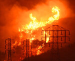 FILE - This Dec. 16, 2017 file photo provided by the Santa Barbara County Fire Department shows flames burning near power lines in Montecito, Calif. A California commission set up to study wildfire issues is strongly recommending that the state change a liability standard imperiling major utilities in a report released Wednesday, May 29, 2019. But Democratic leaders say they won't tackle the hot-button topic for now. (Mike Eliason/Santa Barbara County Fire Department via AP, File)
