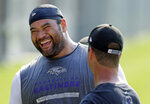 FILE - In this June 17, 2014, file photo, Baltimore Ravens nose tackle Haloti Ngata, left, laughs as he chats with head coach John Harbaugh after an NFL football practice, in Owings Mills, Md. Ngata came into the NFL with Baltimore and will leave as a member of the Ravens, the team that provided him with his best memories and a Super Bowl ring. (AP Photo/Patrick Semansky, File)