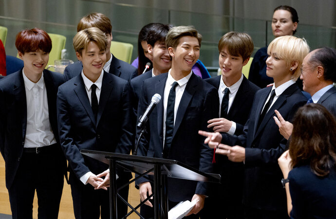 FILE - In this Sept. 24, 2018, file photo, members of the Korean K-Pop group BTS attend a meeting at the U.N. high level event regarding youth during the 73rd session of the United Nations General Assembly, at U.N. headquarters. A Japanese broadcaster canceled a live TV appearance of the Korean band BTS after a photo went viral of a band member wearing a T-shirt showing an atomic bombing juxtaposed with the celebration of Korea's liberation from Japan after World War II. (AP Photo/Craig Ruttle, File)