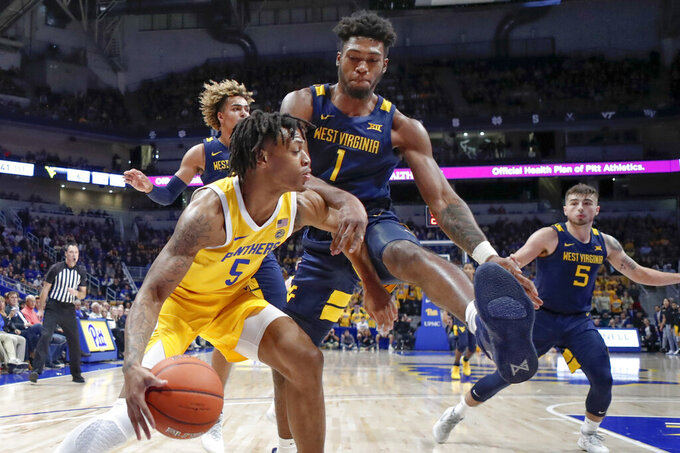 West Virginia's Derek Culver (1) defends as Pittsburgh's Au'Diese Toney (5) drives to the hoop during the first half of an NCAA college basketball game, Friday, Nov. 15, 2019, in Pittsburgh. (AP Photo/Keith Srakocic)
