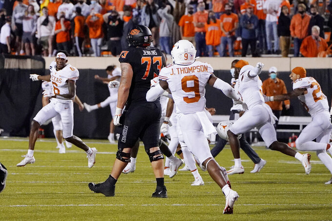 Texas players run onto the field after Texas defeated Oklahoma State 41-34 in overtime of an NCAA college football game in Stillwater, Okla., Saturday, Oct. 31, 2020. (AP Photo/Sue Ogrocki)