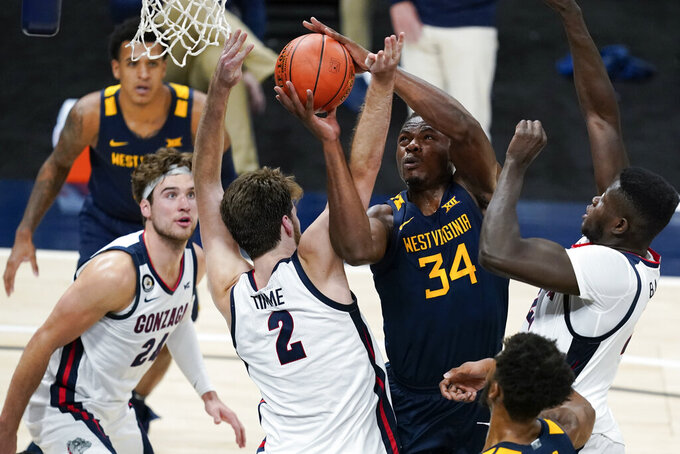 West Virginia's Oscar Tshiebwe (34) is fouled by Gonzaga's Drew Timme (2) during the first half of an NCAA college basketball game Wednesday, Dec. 2, 2020, in Indianapolis. (AP Photo/Darron Cummings)