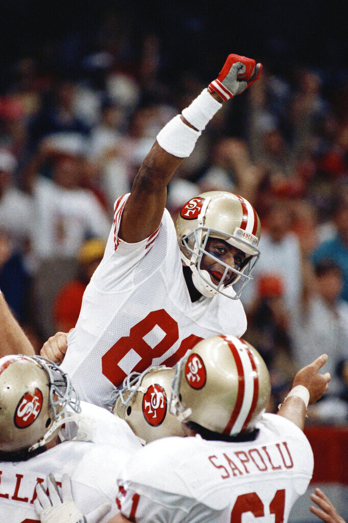 FILE - In this Jan. 28, 1990, file photo, San Francisco 49ers wide receiver Jerry Rice raises his fist in jubilation as he celebrates with teammates Bruce Collie, Left, and Jesse Sapolu after scoring his second touchdown of the day with 34 seconds left in the second quarter at Super Bowl XXIV in New Orleans. The San 49ers ruled most of the 1980s by winning Super Bowls after the 1981, '84, '88 and '89 seasons. (AP Photo/John Gapps III, File)