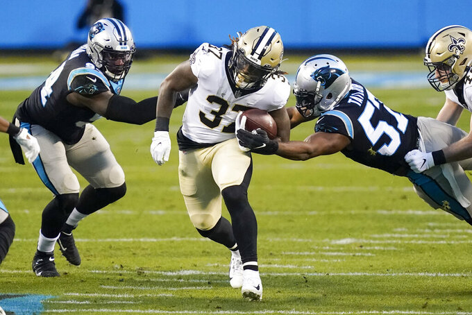 New Orleans Saints running back Tony Jones runs between Carolina Panthers defensive end Efe Obada, left, and outside linebacker Adarius Taylor during the first half of an NFL football game Sunday, Jan. 3, 2021, in Charlotte, N.C. (AP Photo/Gerry Broome)
