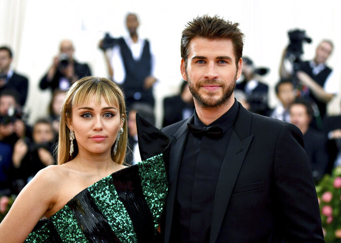 FILE - In this May 6, 2019 file photo, Miley Cyrus, left, and Liam Hemsworth attend The Metropolitan Museum of Art's Costume Institute benefit gala celebrating the opening of the